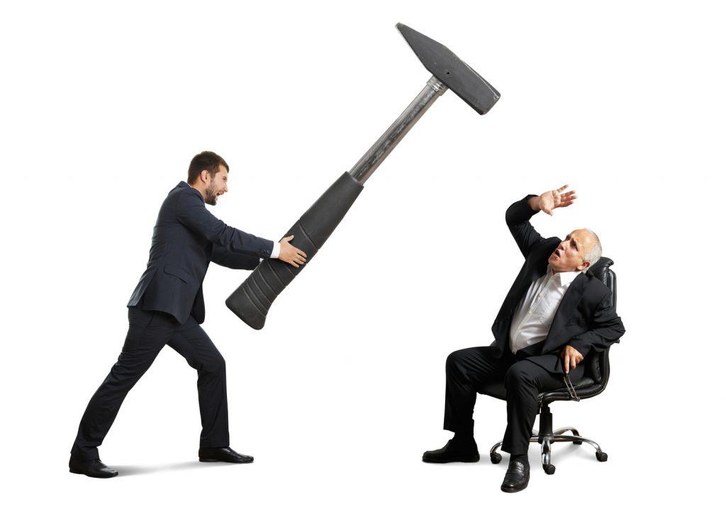 junge führungskraft bedroht älteren mitarbeiter mit einem großen hammer