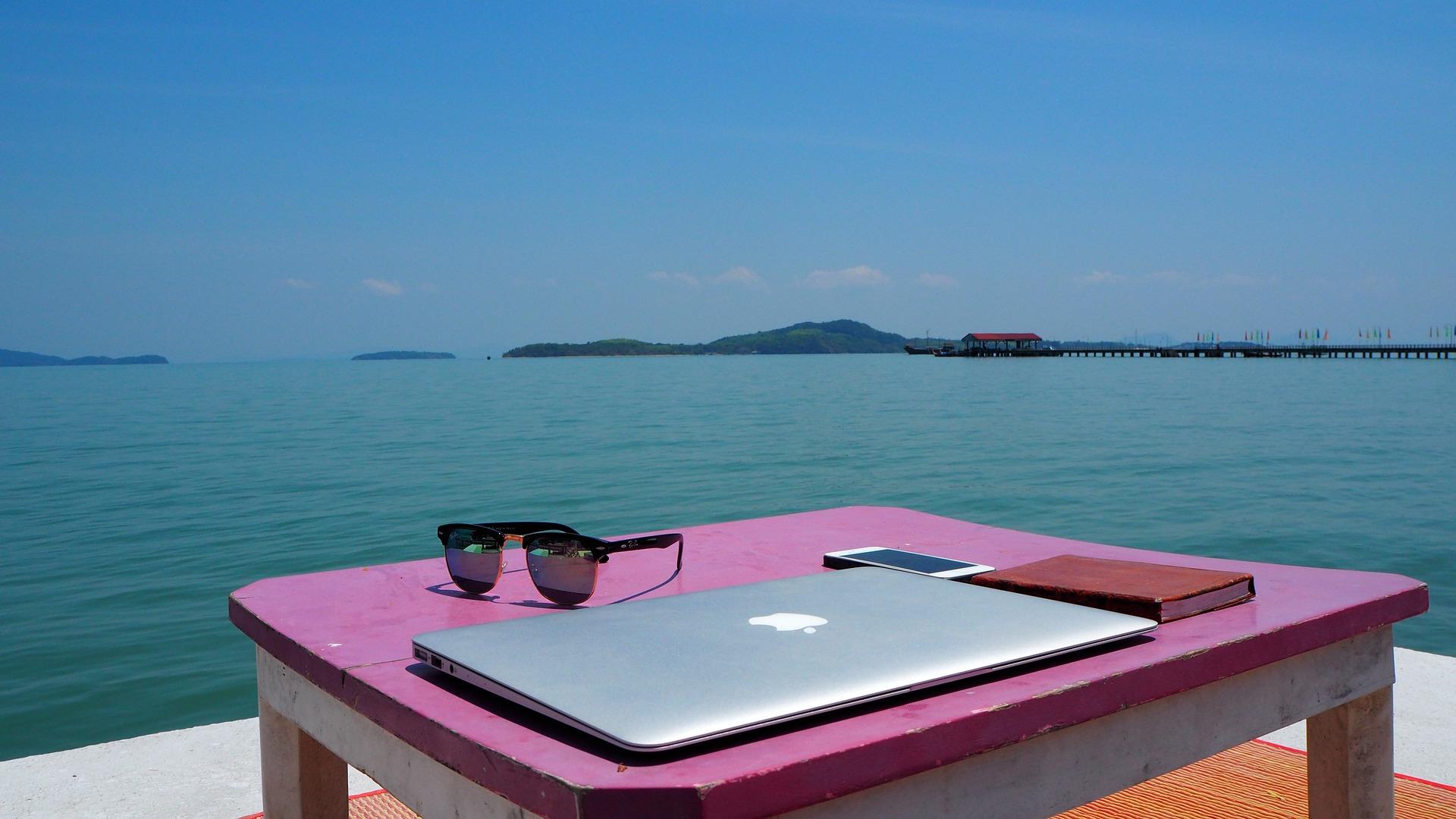 mit Laptop und Handy am Strand arbeiten, Foto CC0 Pixabay